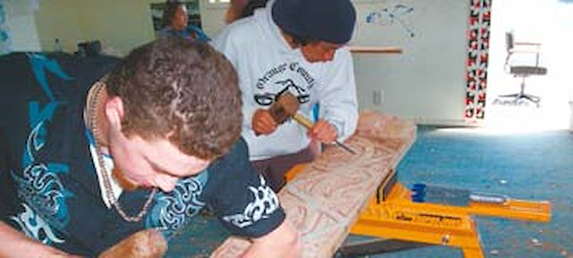 Young Maori doing carving