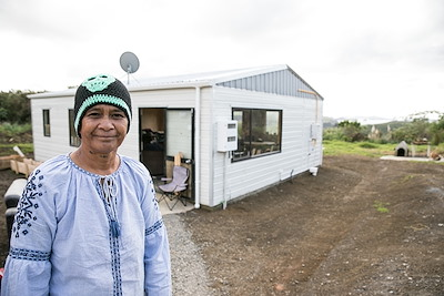 Georgina Taiapo in front of her repaired whare in Takou Bay.