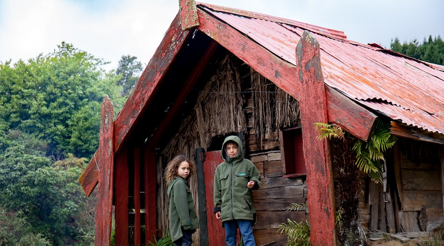 Two tamariki playing in front of a whare at Maungapōhatu. Photographer: Josie McClutchie.